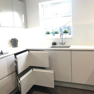 Mid-sized contemporary u-shaped separate kitchen in Buckinghamshire with an undermount sink, flat-panel cabinets, grey cabinets, quartzite benchtops, white splashback, glass sheet splashback, panelled appliances, vinyl floors, a peninsula, grey floor and white benchtop.