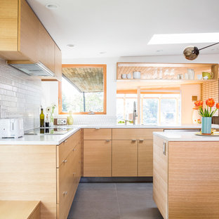 Mid-sized mid-century modern eat-in kitchen photos - Example of a mid-sized 1950s l-shaped eat-in kitchen design in Seattle with an undermount sink, flat-panel cabinets, light wood cabinets, quartz countertops, white backsplash, glass tile backsplash, stainless steel appliances and an island
