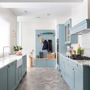 Idéer för att renovera ett mellanstort lantligt vit vitt parallellkök, med granitbänkskiva, vitt stänkskydd, en rustik diskho, skåp i shakerstil, blå skåp och grått golv