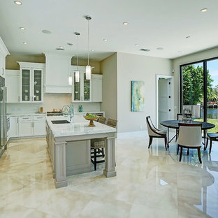 Photo of a mid-sized tropical l-shaped eat-in kitchen in Miami with an undermount sink, recessed-panel cabinets, white cabinets, quartz benchtops, white splashback, porcelain splashback, stainless steel appliances, marble floors, with island and beige floor.