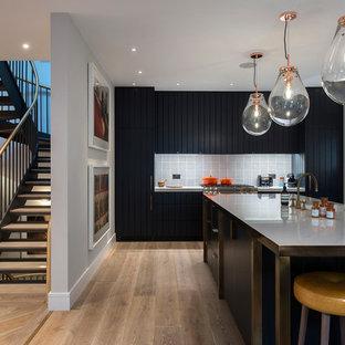 Photo of a modern l-shaped kitchen in London with light hardwood flooring, an island, beige floors, flat-panel cabinets, black cabinets, stainless steel worktops, grey splashback, ceramic splashback, integrated appliances and grey worktops.