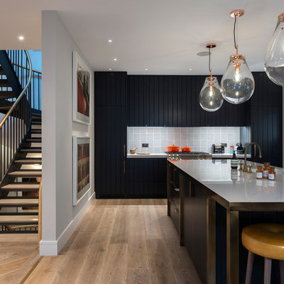 Example of a minimalist l-shaped light wood floor and beige floor kitchen design in London with an island, flat-panel cabinets, black cabinets, stainless steel countertops, gray backsplash, ceramic backsplash, paneled appliances and gray countertops