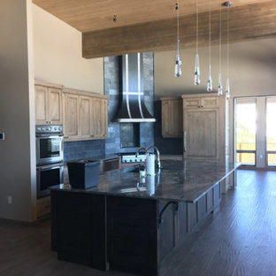 Photo of a mid-sized country single-wall open plan kitchen in Other with an undermount sink, shaker cabinets, medium wood cabinets, granite benchtops, grey splashback, slate splashback, stainless steel appliances, dark hardwood floors, with island and brown floor.