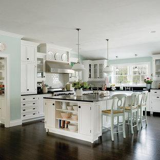シャーロットの大きいエクレクティックスタイルのおしゃれなキッチン (エプロンフロントシンク、シェーカースタイル扉のキャビネット、白いキャビネット、白いキッチンパネル、サブウェイタイルのキッチンパネル、シルバーの調理設備の、濃色無垢フローリング) の写真