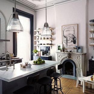 ソルトレイクシティの中サイズのヴィクトリアン調のおしゃれなキッチン (ドロップインシンク、落し込みパネル扉のキャビネット、黒いキャビネット、大理石カウンター、白いキッチンパネル、サブウェイタイルのキッチンパネル、シルバーの調理設備の、淡色無垢フローリング、茶色い床) の写真