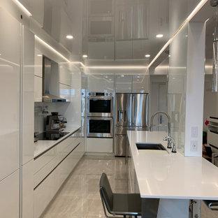 Ejemplo de cocina de galera, minimalista, abierta, con armarios con paneles lisos, puertas de armario blancas, suelo de baldosas de porcelana, una isla, suelo beige, encimeras blancas y papel pintado