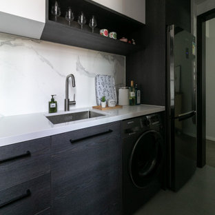 This is an example of a small modern l-shaped separate kitchen in Hong Kong with a drop-in sink, flat-panel cabinets, black cabinets, limestone benchtops, white splashback, marble splashback, black appliances, ceramic floors, no island, grey floor and white benchtop.
