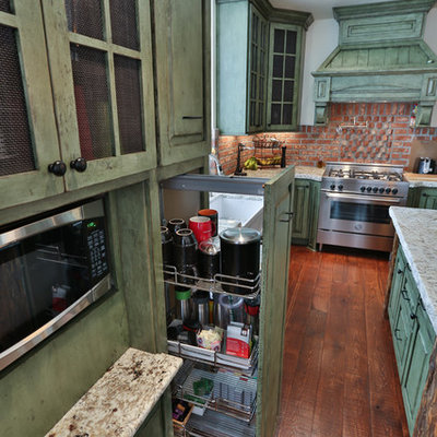 Example of a mid-sized eclectic l-shaped medium tone wood floor eat-in kitchen design in Portland with a farmhouse sink, raised-panel cabinets, green cabinets, granite countertops, red backsplash, stainless steel appliances and an island