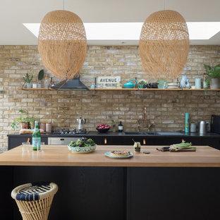 Coastal single-wall kitchen with a double-bowl sink, flat-panel cabinets, black cabinets, wood worktops, brown splashback, brick splashback, light hardwood flooring, an island, beige floors and beige worktops.