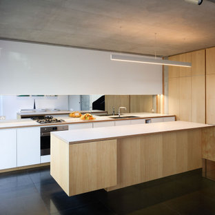 Photo of a large modern galley eat-in kitchen in Sydney with an undermount sink, light wood cabinets, laminate benchtops, mirror splashback, stainless steel appliances, with island, black floor and white benchtop.