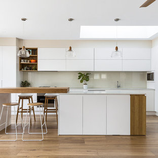 Design ideas for a large modern l-shaped open plan kitchen in Sydney with an undermount sink, flat-panel cabinets, white cabinets, glass sheet splashback, stainless steel appliances, medium hardwood floors, with island, quartz benchtops, white splashback, white benchtop and brown floor.