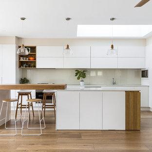シドニーの広いモダンスタイルのおしゃれなキッチン (アンダーカウンターシンク、フラットパネル扉のキャビネット、白いキャビネット、ガラス板のキッチンパネル、シルバーの調理設備、無垢フローリング、クオーツストーンカウンター、白いキッチンパネル、白いキッチンカウンター、茶色い床) の写真