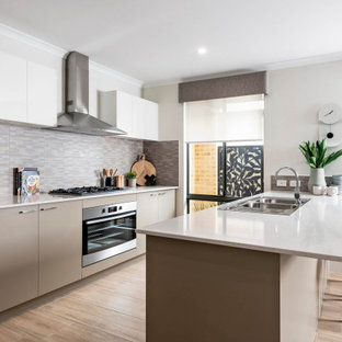 Design ideas for a contemporary galley kitchen in Perth with a drop-in sink, flat-panel cabinets, grey cabinets, grey splashback, stainless steel appliances, a peninsula, beige floor and white benchtop.