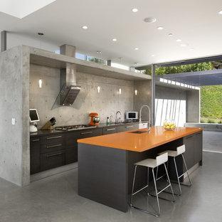 ロサンゼルスのモダンスタイルのおしゃれなキッチン (アンダーカウンターシンク、フラットパネル扉のキャビネット、茶色いキャビネット、オレンジのキッチンカウンター) の写真