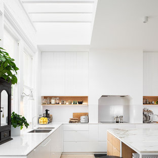 Inspiration for a large beach style l-shaped open plan kitchen in Hobart with an undermount sink, flat-panel cabinets, white cabinets, white splashback, light hardwood floors, with island, beige floor, white benchtop, marble benchtops and white appliances.