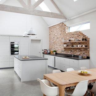 リムリックの大きいコンテンポラリースタイルのおしゃれなキッチン (アンダーカウンターシンク、フラットパネル扉のキャビネット、グレーのキャビネット、珪岩カウンター、赤いキッチンパネル、レンガのキッチンパネル、パネルと同色の調理設備、コンクリートの床、グレーの床、グレーのキッチンカウンター) の写真