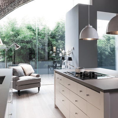 Trendy galley medium tone wood floor and brown floor open concept kitchen photo in London with an undermount sink, flat-panel cabinets, white cabinets, red backsplash, brick backsplash and an island