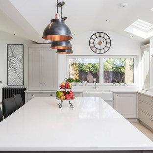 バークシャーのトランジショナルスタイルのおしゃれなキッチン (エプロンフロントシンク、シェーカースタイル扉のキャビネット、ベージュのキャビネット、ミラータイルのキッチンパネル、黒い調理設備、ベージュの床、白いキッチンカウンター) の写真