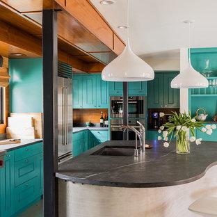 Foto di una grande cucina boho chic con lavello sottopiano, ante a filo, ante blu, elettrodomestici in acciaio inossidabile, isola, top in saponaria, paraspruzzi marrone, paraspruzzi in legno e top nero