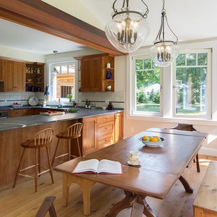 Mid-sized farmhouse eat-in kitchen ideas - Inspiration for a mid-sized country u-shaped medium tone wood floor eat-in kitchen remodel in Boston with an undermount sink, shaker cabinets, medium tone wood cabinets, granite countertops, white backsplash, porcelain backsplash, stainless steel appliances and a peninsula