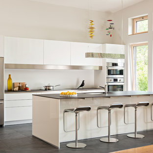 Example of a mid-sized trendy galley ceramic floor and gray floor kitchen design in Boston with an undermount sink, flat-panel cabinets, white cabinets, quartz countertops, stainless steel appliances and an island