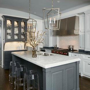 Bild på ett vintage kök, med en dubbel diskho, luckor med infälld panel, vita skåp, flerfärgad stänkskydd, rostfria vitvaror, mörkt trägolv och en köksö