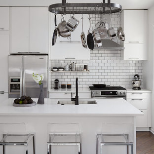 Small contemporary kitchen remodeling - Inspiration for a small contemporary galley dark wood floor and brown floor kitchen remodel in Chicago with an undermount sink, flat-panel cabinets, white cabinets, quartz countertops, white backsplash, ceramic backsplash, stainless steel appliances, an island and white countertops