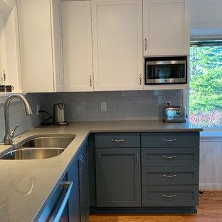 シアトルの小さいモダンスタイルのおしゃれなキッチン (アンダーカウンターシンク、シェーカースタイル扉のキャビネット、青いキャビネット、クオーツストーンカウンター、青いキッチンパネル、サブウェイタイルのキッチンパネル、シルバーの調理設備の、淡色無垢フローリング、黄色い床、グレーのキッチンカウンター) の写真