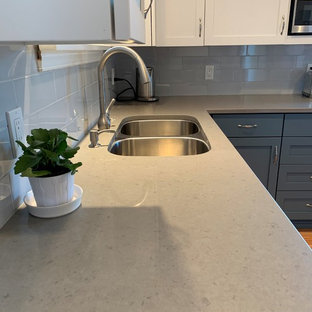 Small modern u-shaped separate kitchen in Seattle with an undermount sink, shaker cabinets, white cabinets, quartz benchtops, blue splashback, subway tile splashback, stainless steel appliances, light hardwood floors, yellow floor and grey benchtop.