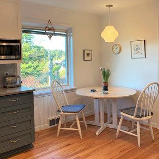 Foto på ett avskilt, litet funkis grå u-kök, med en undermonterad diskho, skåp i shakerstil, blå skåp, bänkskiva i kvarts, blått stänkskydd, stänkskydd i tunnelbanekakel, rostfria vitvaror, ljust trägolv och gult golv