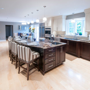 Huge transitional open concept kitchen appliance - Huge transitional l-shaped light wood floor open concept kitchen photo in Providence with an island, shaker cabinets, white cabinets, granite countertops, beige backsplash, stone tile backsplash, stainless steel appliances and an undermount sink