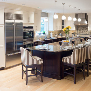 Huge traditional open concept kitchen photos - Huge elegant l-shaped light wood floor open concept kitchen photo in Providence with stainless steel appliances, granite countertops, an island, shaker cabinets, white cabinets, beige backsplash, stone tile backsplash and an undermount sink