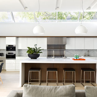 This is an example of a contemporary single-wall open plan kitchen in Chicago with a triple-bowl sink, flat-panel cabinets, white cabinets, grey splashback, stone slab splashback, stainless steel appliances, light hardwood floors, with island, beige floor and grey benchtop.