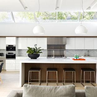Idéer för ett modernt grå linjärt kök med öppen planlösning, med en trippel diskho, släta luckor, vita skåp, grått stänkskydd, stänkskydd i sten, rostfria vitvaror, ljust trägolv, en köksö och beiget golv