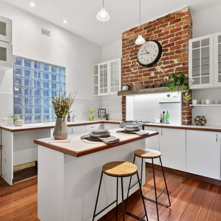 Mid-sized country l-shaped kitchen in Perth with flat-panel cabinets, white cabinets, glass tile splashback, medium hardwood floors, brown floor, white benchtop, a double-bowl sink, wood benchtops, white splashback and with island.