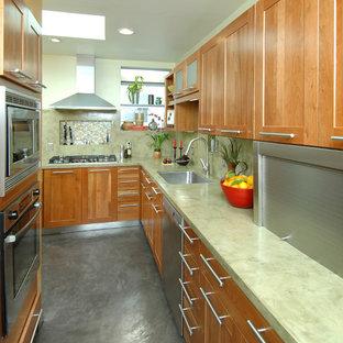 サンフランシスコの中くらいのアジアンスタイルのおしゃれなキッチン (ドロップインシンク、落し込みパネル扉のキャビネット、中間色木目調キャビネット、コンクリートカウンター、緑のキッチンパネル、シルバーの調理設備、コンクリートの床) の写真
