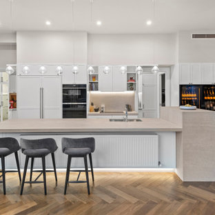 Inspiration for a large contemporary galley open plan kitchen in Melbourne with an undermount sink, recessed-panel cabinets, white cabinets, grey splashback, panelled appliances, medium hardwood floors, with island, brown floor, beige benchtop, granite benchtops and granite splashback.