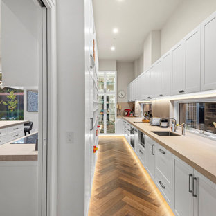 Photo of a large contemporary galley kitchen pantry in Melbourne with a single-bowl sink, recessed-panel cabinets, white cabinets, window splashback, stainless steel appliances, medium hardwood floors, no island, brown floor, beige benchtop and granite benchtops.