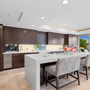 Tropical kitchen remodeling - Island style beige floor kitchen photo in Orange County with flat-panel cabinets, dark wood cabinets, beige backsplash, paneled appliances, an island and white countertops
