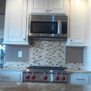 Small southwestern kitchen designs - Example of a small southwest single-wall ceramic floor kitchen design in Houston with a double-bowl sink, recessed-panel cabinets, white cabinets, granite countertops, multicolored backsplash, stone tile backsplash, stainless steel appliances and no island