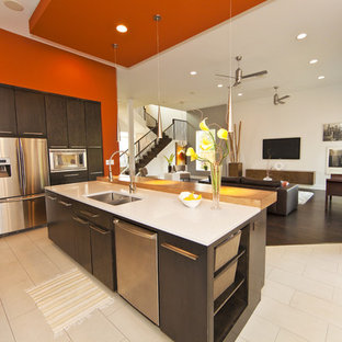 Open concept kitchen - mid-sized contemporary single-wall porcelain floor and beige floor open concept kitchen idea in Houston with stainless steel appliances, a double-bowl sink, flat-panel cabinets, dark wood cabinets, quartz countertops and an island