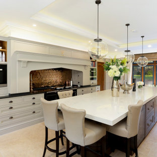 This is an example of a large classic galley kitchen in Kent with recessed-panel cabinets, an island, white cabinets, metallic splashback, black appliances, beige floors and black worktops.