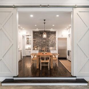 Große Country Wohnküche in U-Form mit Schrankfronten im Shaker-Stil, weißen Schränken, Küchenrückwand in Grau, Küchengeräten aus Edelstahl, dunklem Holzboden, braunem Boden und Kücheninsel in Houston