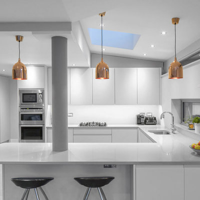 Eat-in kitchen - mid-sized contemporary u-shaped ceramic tile eat-in kitchen idea in Dublin with an integrated sink, shaker cabinets, white cabinets, solid surface countertops, white backsplash, paneled appliances and a peninsula