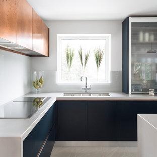 Mittelgroße Moderne Wohnküche mit flächenbündigen Schrankfronten, blauen Schränken, Quarzit-Arbeitsplatte, Küchenrückwand in Weiß, Elektrogeräten mit Frontblende, Kücheninsel und Triple-Waschtisch in London