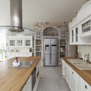 シドニーの広いシャビーシック調のおしゃれなキッチン (シルバーの調理設備、ドロップインシンク、白いキャビネット、木材カウンター、白いキッチンパネル、セラミックタイルのキッチンパネル、セラミックタイルの床、レイズドパネル扉のキャビネット、茶色い床、茶色いキッチンカウンター) の写真