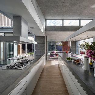 Foto på ett stort funkis kök, med en undermonterad diskho, släta luckor, vita skåp, rostfria vitvaror, bänkskiva i betong, vitt stänkskydd, stänkskydd i marmor, travertin golv, en köksö och gult golv