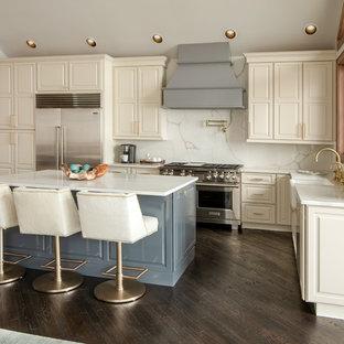 シャーロットの大きいラスティックスタイルのおしゃれなキッチン (エプロンフロントシンク、レイズドパネル扉のキャビネット、ベージュのキャビネット、白いキッチンパネル、石スラブのキッチンパネル、シルバーの調理設備の、濃色無垢フローリング、茶色い床、白いキッチンカウンター) の写真