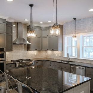 他の地域の大きいインダストリアルスタイルのおしゃれなキッチン (グレーのキャビネット、御影石カウンター、ダブルシンク、シェーカースタイル扉のキャビネット、白いキッチンパネル、サブウェイタイルのキッチンパネル、シルバーの調理設備の、グレーの床) の写真