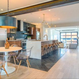 デンバーのインダストリアルスタイルのおしゃれなキッチン (フラットパネル扉のキャビネット、中間色木目調キャビネット、グレーのキッチンパネル、シルバーの調理設備、淡色無垢フローリング) の写真